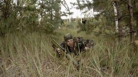 Солдат подготавливает RPG лежа в траве, и после этого направляя акции видеоматериалы