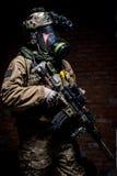 Солдат с винтовкой и респиратор на темной предпосылке стоковая фотография