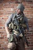 Солдат с винтовкой на предпосылке кирпичей стоковое изображение rf