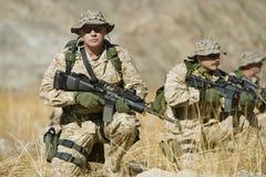 Солдат с винтовкой пока команда патрулируя во время войны Стоковая Фотография