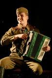 Солдат Portra советский, герой в форме Второй Мировой Войны играя аккордеон над черной предпосылкой Стоковое Изображение RF