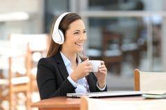 Содержание исполнительной власти слушая тональнозвуковое в кофейне Стоковая Фотография
