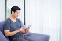 содержание средств массовой информации бизнесмена наблюдая в таблетке сидя на софе Стоковое фото RF