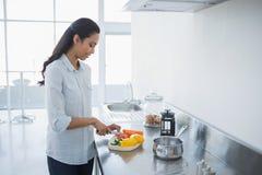 Содержимая женщина подготавливая салат стоя в яркой кухне Стоковые Изображения