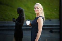 Содержимая коммерсантка держа чашку кофе Стоковое Фото