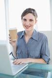 Содержимая коммерсантка показывая устранимую чашку сидя на ее столе Стоковые Фото
