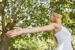 Содержимая молодая женщина делая йогу в парке Стоковые Изображения