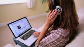 Содержимое привлекательное брюнет сидя на кресле слушая к музыке сток-видео