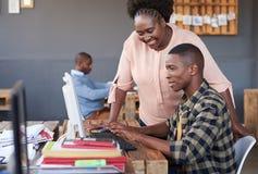 Содержимые африканские бизнесмены говоря совместно над компьютером Стоковое Фото
