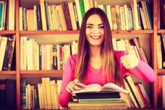 Содержимый студент девушки в библиотеке колледжа Стоковое Фото