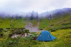 Солитарный туристский шатер стоит на луге Стоковая Фотография
