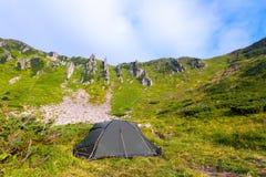 Солитарный туристский шатер стоит на луге Стоковые Изображения