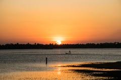Солнечность в вечере, имеет рыболова внутри реки, bac захода солнца стоковые фото