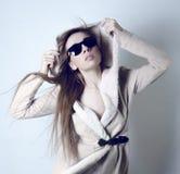 Солнечные очки девушки нося и белая меховая шыба Стоковая Фотография