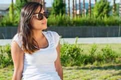 Солнечные очки девушки нося представляя в парке в солнечном свете Стоковое Изображение