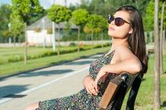 Солнечные очки девушки нося представляя в парке в солнечном свете Стоковые Фотографии RF