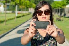 Солнечные очки девушки нося принимая selfie снаружи в парке Стоковые Изображения RF