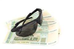Солнечные очки и белорусские деньги людей стоковые изображения