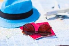 Солнечные очки и пасспорты, миниатюрный самолет дальше Стоковое фото RF
