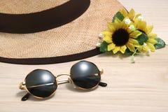 Солнечные очки и соломенная шляпа с солнцецветами на древесине стоковое изображение