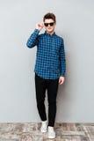 Солнечные очки красивого человека нося стоя над серой стеной стоковые изображения rf