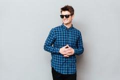 Солнечные очки красивого человека нося стоя над серой стеной стоковые изображения
