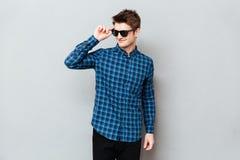 Солнечные очки молодого человека нося стоя над серой стеной стоковое изображение rf