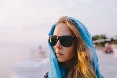 Солнечные очки молодой женщины нося и голубой шарф Стоковая Фотография RF
