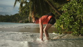 Солнечные очки молодой женщины нося ослабляя на тропическом пляже сток-видео