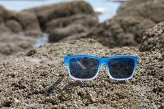 Солнечные очки на каменном взморье Стоковая Фотография RF