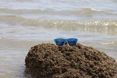 Солнечные очки на каменном взморье Стоковые Изображения