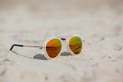 Солнечные очки на песчаном пляже в лете каникула зонтика неба пляжа предпосылки голубая цветастая Стоковое Фото