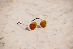 Солнечные очки на песчаном пляже в лете каникула зонтика неба пляжа предпосылки голубая цветастая Стоковое Изображение RF