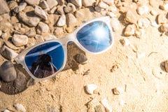 Солнечные очки на скалистом пляже Стоковое Изображение