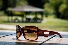 Солнечные очки на таблице в солнце на деревянном столе Стоковая Фотография