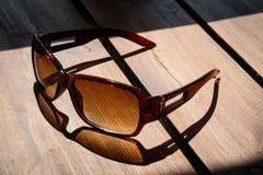 Солнечные очки на таблице в солнце на деревянном столе Стоковые Фото