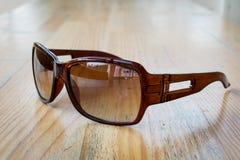 Солнечные очки на таблице в солнце на деревянном столе Стоковое Изображение RF
