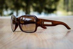 Солнечные очки на таблице в солнце на деревянном столе Стоковое Фото