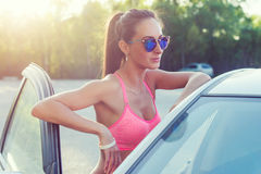 Солнечные очки привлекательной женщины детенышей подходящей нося готовя ее автомобиль smilling показывающ v-знак, жест победы или Стоковые Изображения RF