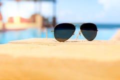 Солнечные очки рядом с бассейном с голубой предпосылкой океана Стоковое Изображение RF