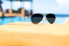 Солнечные очки рядом с бассейном с голубой предпосылкой океана стоковое фото rf