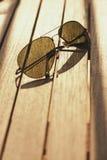 Солнечные очки с поляризатором на деревянном столе Стоковое фото RF