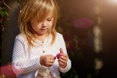 Солнечный день, маленькая девочка лежит на траве Стоковые Фотографии RF