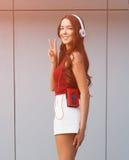 Солнечный портрет азиатской девушки в красном верхе и белых шортах, наушниках и с винтажный представлять игрока кассеты Стоковые Фото