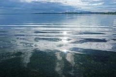 Солнечный свет отраженный на спокойной воде с облачным небом Стоковые Фото
