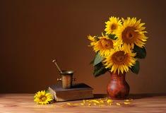 Солнцецветы в керамической вазе и книгах Стоковые Фото