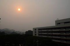 Солнце вечера Сингапура, который заволокло загрязнение помоха Стоковое Фото