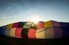 Солнце выступая над надувая конвертом горячего воздушного шара Стоковая Фотография RF