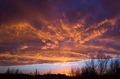 Солнце идет вниз над городским ландшафтом Стоковая Фотография