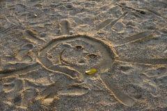 Солнце нарисованное на песке и лист осени положительно стоковая фотография rf
